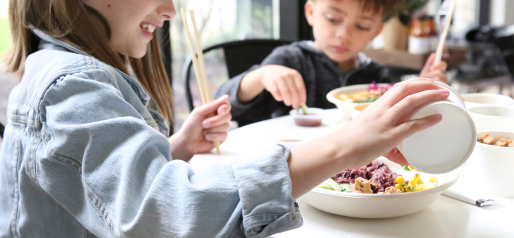 A Charley's Foundation picture showing two children eating BIBIBOP bowls with chopsticks.