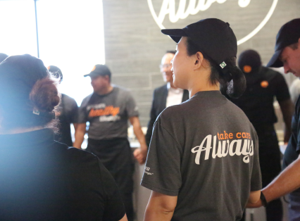 The back of a BIBIBOP Asian Grill employee standing in a team huddle wearing a BIBIBOP shirt saying: Take care always