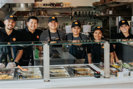 Six BIBIBOP Asian Grill employees standing behind a Build Your Own BIBIBOP Bowl restaurant counter smiling at the camera